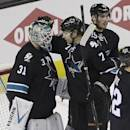 San Jose Sharks goalie Antti Niemi, left, is congratulated by Brad Stuart (7) and James Sheppard (15) at the end of Game 1 of an NHL hockey first-round playoff series Thursday, April 17, 2014, in San Jose, Calif. San Jose won, 6-3. (AP Photo/Ben Margot)