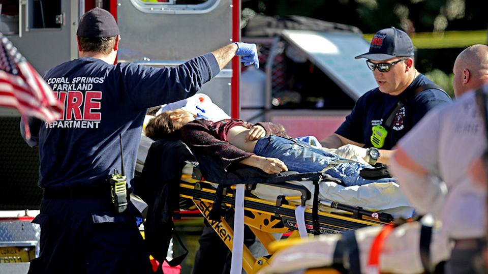 A woman is rushed from the school by paramedics after the shooting. 17 people died after being shot. Source Getty