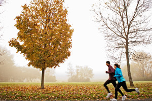 USA --- Couple running on foggy autumn morning --- Image by © Ocean/Corbis