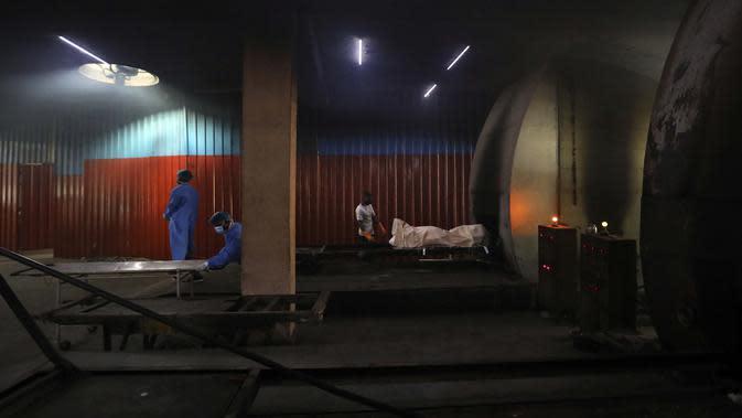 Pekerja melepas tandu saat orang lain bersiap untuk mengkremasi jenazah korban COVID-19 di New Delhi, India, Rabu (16/9/2020). Total infeksi virus corona di India melewati 5 juta pada Rabu (16/9). (AP Photo/Manish Swarup)
