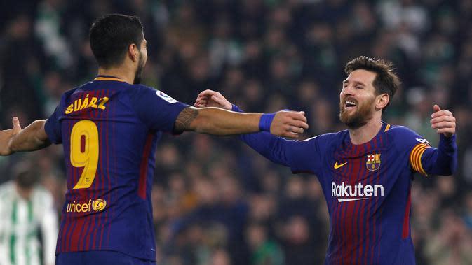 Pemain Barcelona, Lionel Messi dan rekan setimnya Luis Suarez merayakan gol ke gawang Real Betis pada pertandingan lanjutan La Liga di Stadion Benito Villamarin, Minggu (21/1). Barcelona menang telak 5-0 atas tuan rumah Real Betis. (AP/Miguel Morenatti)