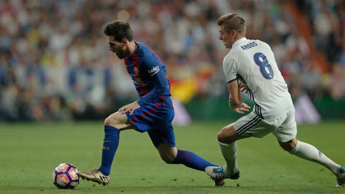 Lionel Messi (kiri) berusaha membawa bola dari kawalan gelandang Real Madrid, Toni Kroos dalam el clasico La Liga Spanyol di Stadion Santiago Bernabeu, Madrid, (24/4). Barcelona menang atas Real Madrid dengan skor 3-2. (AP Photo/Daniel Ochoa de Olza)
