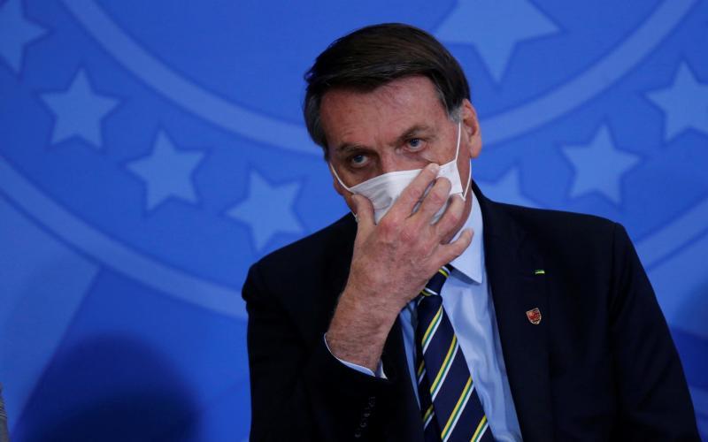 Jair Bolsonaro adjusts his protective face mask - Reuters