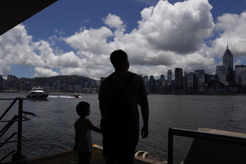 People walk at the waterfront of the Victoria Harbor of Hong Kong, Saturday, June 20, 2020. China's top legislative body has taken up a draft national security law for Hong Kong that has been strongly criticized as undermining the semi-autonomous territory's legal and political institutions. (AP Photo/Kin Cheung)