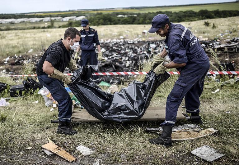 Ukrainian emergency service workers collect bodies of victims of flight MH17 at the crash site near Grabove, on July 20, 2014