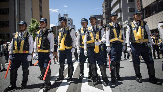 Petugas kepolisian Jepang berjaga selama Festival Sanja Matsuri di luar kuil Sensoji, distrik Asakusa, Tokyo, Minggu (20/5). Sanja Matsuri adalah festival tahunan di distrik Asakusa yang diadakan pada akhir pekan ketiga pada bulan Mei (AFP/Behrouz MEHRI)