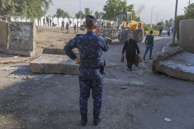 An Iraqi police officer instructs a bulldozer while Iraqi security forces remove cement blocks and opened the streets, that were closed for security concerns, around the Green Zone in Baghdad, Iraq, Thursday, Jan. 2, 2020. Iran-backed militiamen have withdrawn from the U.S. Embassy compound in Baghdad after two days of clashes with U.S. security forces. (AP Photo/Nasser Nasser)
