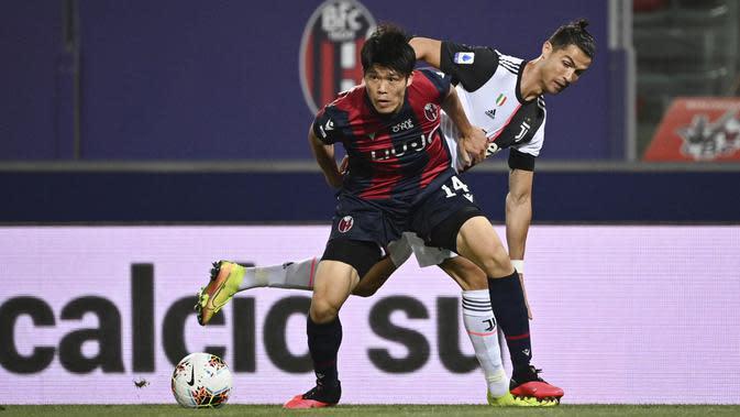 Striker Juventus, Cristiano Ronaldo, berebut bola dengan pemain Bologna, Takehiro Tomiyasu, pada laga Serie A di Stadion Renato Dall'Ara, Senin (22/6/2020). Juventus menang 2-0 atas Bologna. (AP/Massimo Paolone)