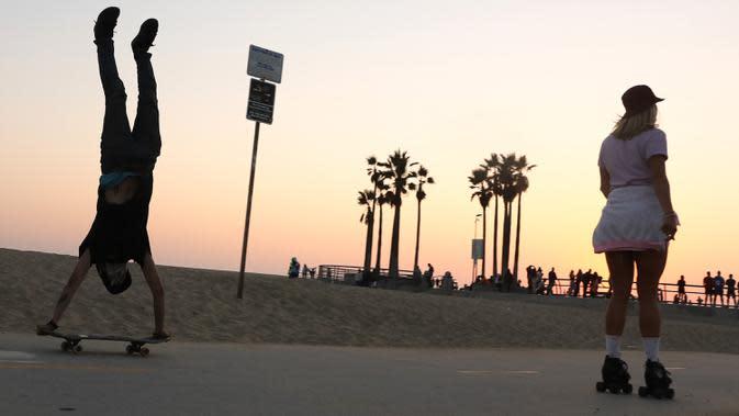 Seorang perempuan mengenakan sepatu roda di dekat pemain skateboard di sepanjang Venice Beach di Venice, California, Kamis (3/9/2020). Permintaan sepatu roda di Amerika Serikat mengalami peningkatan tajam di tengah pembatasan sosial akibat corona Covid-19. (Mario Tama/Getty Images/AFP)