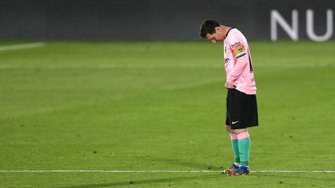 Striker Barcelona, Lionel Messi, tertunduk lesu usai ditaklukkan Getafe pada laga Liga Spanyol di Stadion Coliseum Alfonso Perez, Minggu (18/10/2020). Barcelona takluk dengan skor 1-0. (AP/Manu Fernandez)