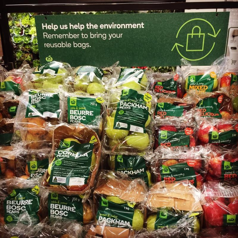 Apples wrapped in plastic are seen in a Woolworths supermarket underneath a sign about using reusable bags. Source: Facebook