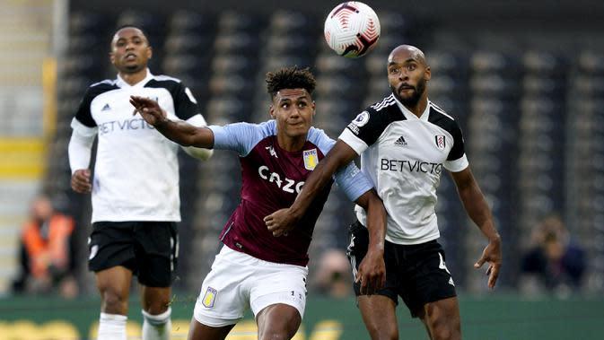 Penyerang Aston Villa, Ollie Watkins, berebut bola dengan bek Fulham, Denis Odoi, pada laga lanjutan Liga Inggris di Craven Cottage, Selasa (29/9/2020) dini hari WIB. Aston Villa menang 3-0 atas Fulham. (Will Oliver/Pool via AP)