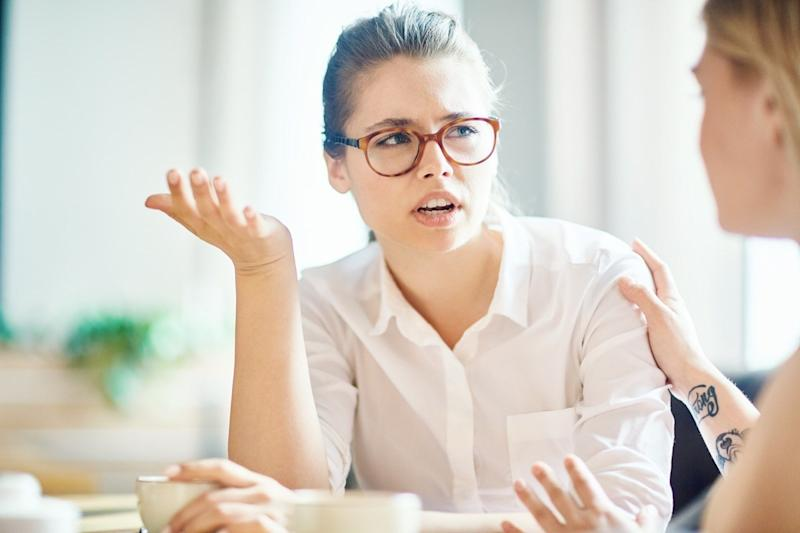 anxious woman explaining reason of her worry to friend by cup of coffee