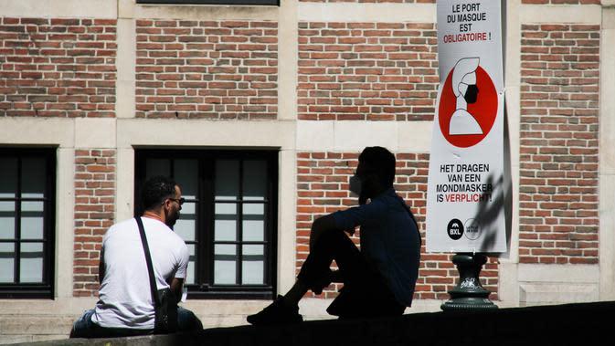 Sejumlah orang beristirahat di dekat spanduk informasi yang mengingatkan masyarakat untuk mengenakan masker di Brussel, Belgia (5/8/2020). Kota Brussel memperluas aturan wajib pakai masker di wilayahnya hingga termasuk di jalan-jalan yang ramai dan zona pejalan kaki. (Xinhua/Zheng Huansong)