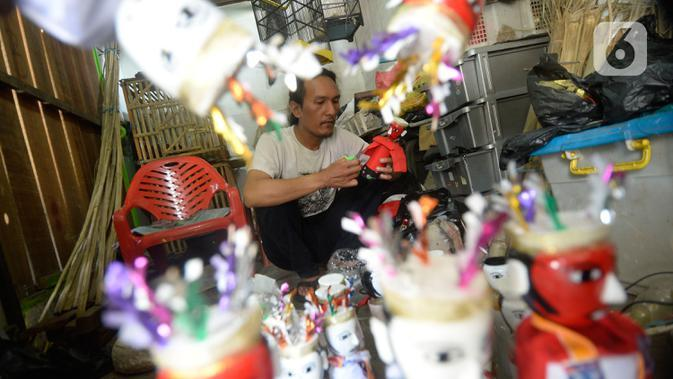 Pengrajin menyelesaikan ondel-ondel hiasan yang terbuat dari limbah plastik botol di Kampung Sawah Lama, Ciputat, Tangerang Selatan, banten, Jumat (4/9/2020). Harga satu perpasang dijual dengan harga Rp 35 ribu, pada saat pandemi ini pemesanan menurut hingga 40 persen. (merdeka.com/Dwi Narwoko)