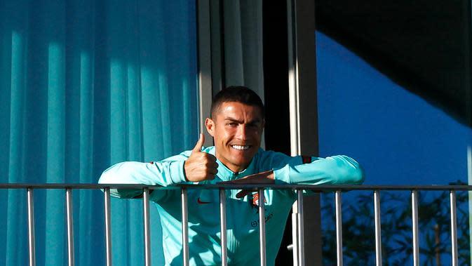 Cristiano Ronaldo yang terjangkit COVID-19 tampak semringah menyaksikan rekan-rekannya di timnas Portugal berlatih dari balkon kamar hotelnya, Selasa (13/10/2020) (AFP/Diogo Pinto)
