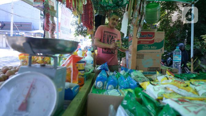 Erdianto (45) pedagang warung sembako tradisional merapikan dagangannya yang dapat dibeli secara langsung maupun pesan antar di Pinggir jalan Villa Pamulang, Tangerang Selatan, Banten, Selasa (25/08/2020). (merdeka.com/Dwi Narwoko)