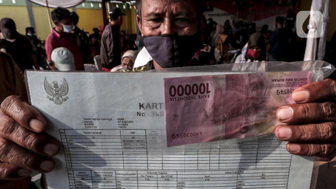 Warga menunjukkan uang tunai usai menerima Bantuan Sosial Tunai (BST) di Desa Cikande, Kecamatan Jayanti, Kabupaten Tangerang, Banten, Selasa (23/6/2020). Bantuan sebesar Rp 600 ribu per keluarga tersebut diharapkan bisa dimanfaatkan untuk membeli kebutuhan mendesak. (Liputan6.com/Johan Tallo)