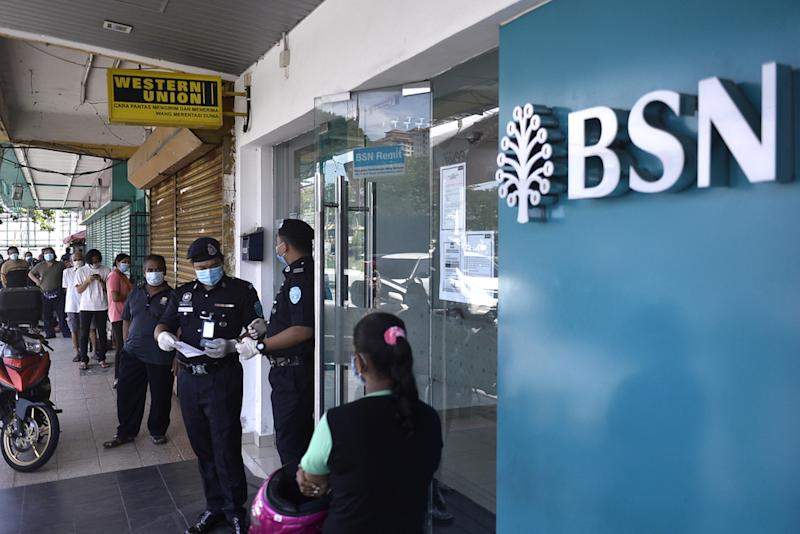 People queue in front of a Bank Simpanan Nasional branch in Kuala Lumpur April 6, 2020. — Picture by Miera Zulyana