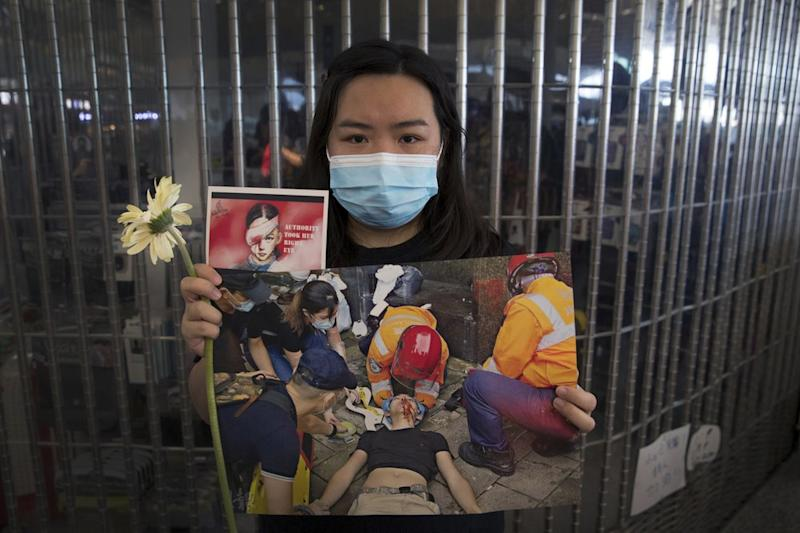 A woman holds a flower and posters showing people injured by police during the Hong Kong protests which have shut down the airport.