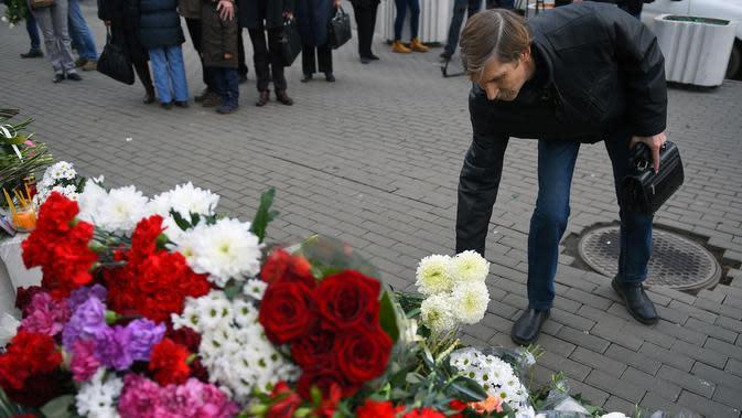 Seorang pria menaruh bunga di luar Kedutaan Besar Prancis di Moskow (4/11/2015). Serangan teroris yang terjadi di Paris telah menewaskan sekitar 140 orang. (AFP PHOTO/DMITRY SEREBRYAKOV)