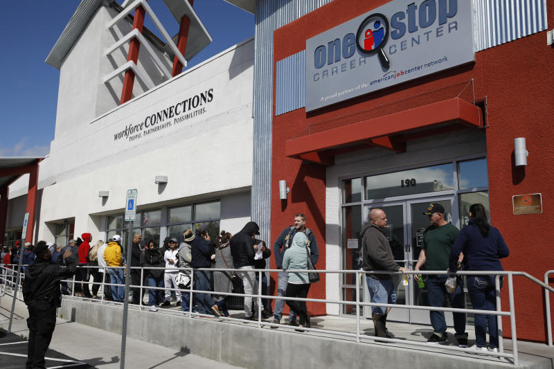 FILE - In this March 17, 2020 file photo, people wait in line for help with unemployment benefits at the One-Stop Career Center in Las Vegas.   A record-high number of people applied for unemployment benefits last week as layoffs engulfed the United States in the face of a near-total economic shutdown caused by the coronavirus. The surge in weekly applications for benefits far exceeded the previous record set in 1982.   (AP Photo/John Locher, File)