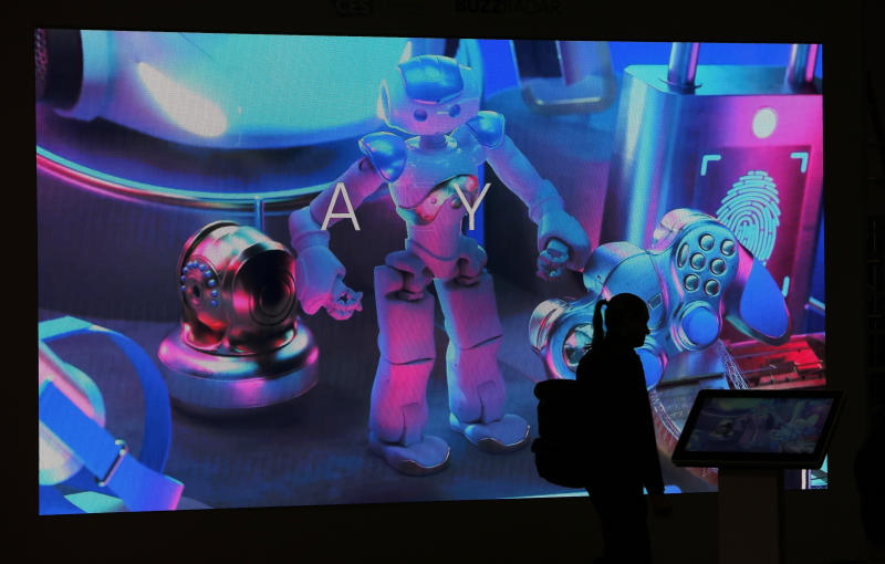 A person walks by a booth display before CES International, Saturday, Jan. 4, 2020, in Las Vegas. (AP Photo/John Locher)