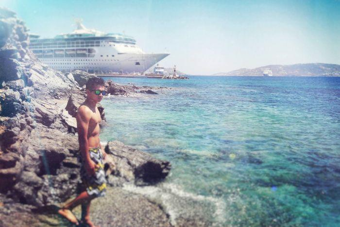 A young man in board shorts on a rocky shore with a cruise ship behind him