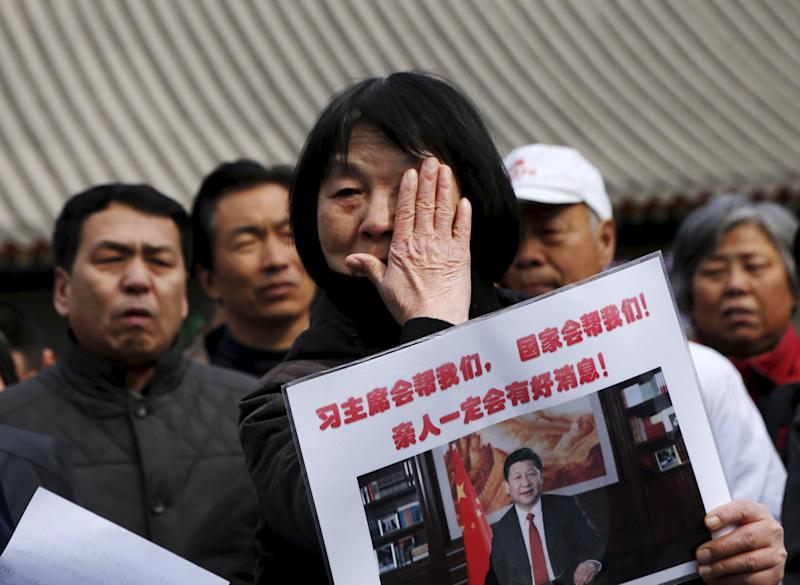 Dai Shuqin, whose family members were onboard Malaysia Airlines flight MH370 which went missing in 2014, wipes away tears as she holds a placard at Lama Temple in Beijing