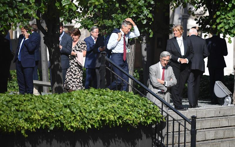 Waiting game: MPs stand in the sunshine before casting their votes - Justin Tallis/AFP