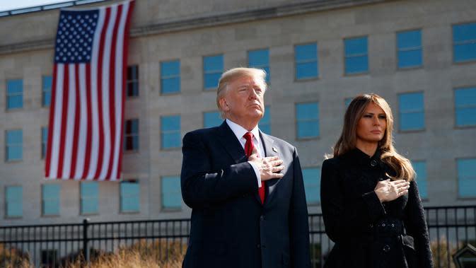 Presiden AS Donald Trump dan Ibu Negara, Melania Trump mengheningkan cipta untuk korban serangan 11 September 2001 dalam acara peringatan di Pentagon, Senin (11/9). Trump untuk pertama kalinya sebagai Presiden memimpin peringatan 9/11. (AP/Evan Vucci)