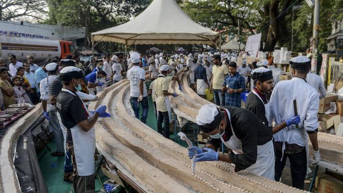 Suasana pembuatan kue sepanjang 6,5 km untuk kue terpanjang dunia, di Thrissur di negara bagian Kerala, India selatan (15/1/2020). Sebelumnya rekor Guinness World Record untuk kue terpanjang diraih di China degan panjang 3,2 kilometer. (AFP/Arun Sankar)