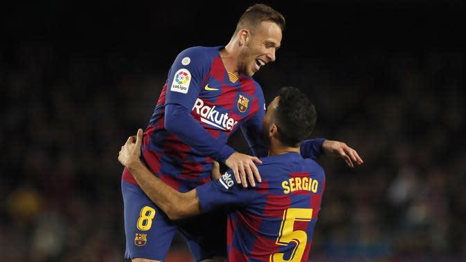 Gelandang Barcelona, Sergio Busquets berselebrasi dengan rekannya Arthur usai mencetak gol ke gawang Celta Vigo pada pertandingan lanjutan La Liga Spanyol di stadion Camp Nou (9/11/2019). Barcelona menang telak 4-1 atas Vigo. (AP Photo/Joan Monfort)