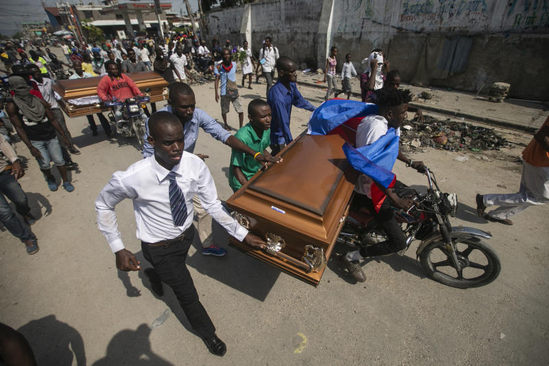Family and friends transport the coffins containing the remains of protesters recently killed, in Port-au-Prince, Haiti, Nov. 19, 2019. The image was part of a series of photographs by Associated Press photographers which was named a finalist for the 2020 Pulitzer Prize for Breaking News Photography. (AP Photo/Dieu Nalio Chery)