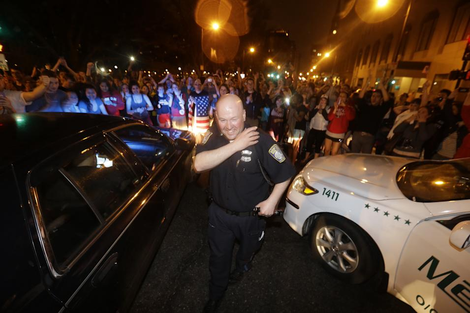 A police officer reacts to news of the arrest of one of the Boston Marathon bombing suspects, Friday, April 19, 2013, in Boston. Boston Marathon bombing suspect Dzhokhar Tsarnaev was captured in Watertown, Mass. The 19-year-old college student wanted in the bombings was taken into custody Friday evening after a manhunt that left the city virtually paralyzed and his older brother and accomplice dead. (AP Photo/Julio Cortez)