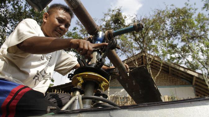 Gambar yang diambil pada 17 November 2019, Jujun Junaedi menyelesaikan pembuatan helikopter buatannya di halaman belakang rumahnya di Sukabumi. Jujun merogoh kocek hingga lebih dari RP 30 juta rupiah untuk merakit helikopter bermesin genset dua silinder 700 cc ini. (Wulung WIDARBA/AFP)