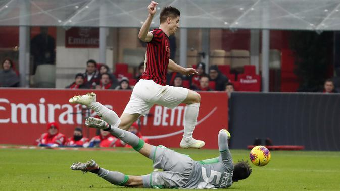 Striker AC Milan Krzysztof Piatek coba melewati kiper Sassuolo Gianluca Pegolo pada laga Serie A di Stadio San Siro, Minggu (15/12/2019). (AP Photo/Antonio Calanni)