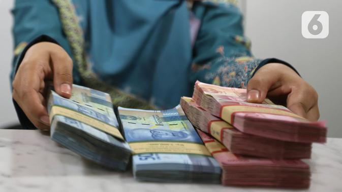 Teller menunjukkan mata uang rupiah di bank, Jakarta, Rabu (22/1/2020). Gubernur Bank Indonesia Perry Warjiyo mengatakan penguatan nilai tukar rupiah yang belakangan terjadi terhadap dolar Amerika Serikat sejalan dengan fundamental ekonomi Indonesia dan mekanisme pasar. (Liputan6.com/Angga Yuniar)