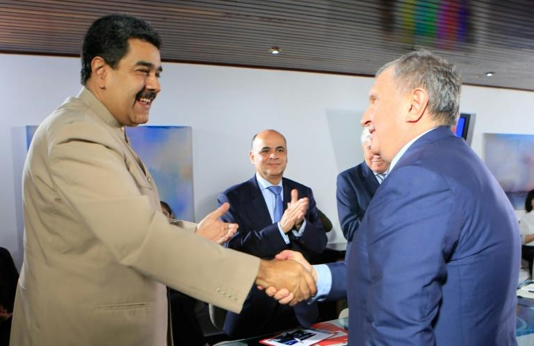 Venezuelan President Nicolas Maduro greets he head of Russian state-owned oil giant Rosneft, Igor Sechin, during a December 2017 meeting in Caracas