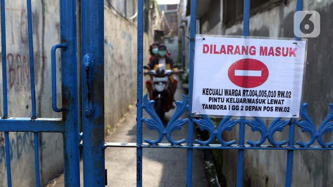 Warga berkendara di salah satu gang yang ditutup secara mandiri di kawasan Tambora, Jakarta, Sabtu (4/4/2020). Penutupan akses masuk kawasan ini untuk membatasi kegiatan warga dan mencegah penyebaran serta penularan virus COVID-19. (Liputan6.com/Helmi Fithriansyah)