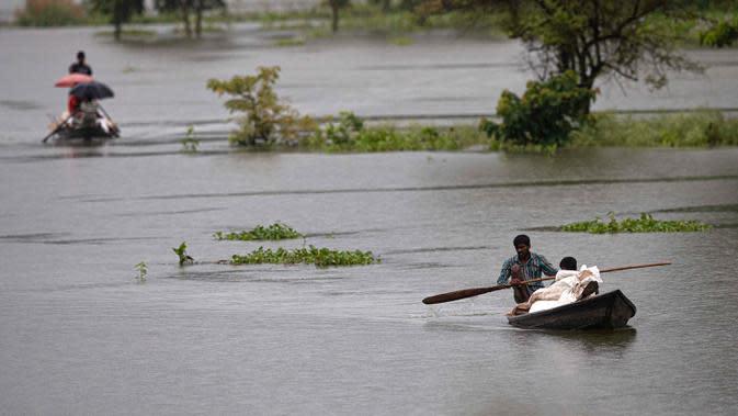 Penduduk desa mendayung perahu-perahu desa dengan barang bawaan mereka untuk pindah ke daerah-daerah yang lebih aman melalui banjir di distrik Morigaon di Assam, India (26/6/2020). (AP Photo/Anupam Nath)