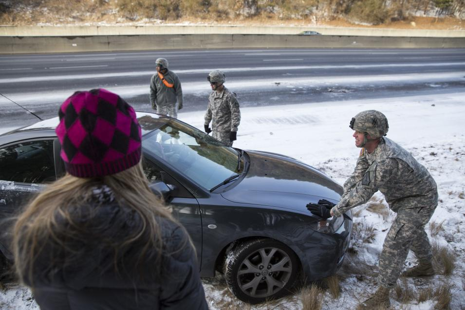 Georgia National Guard troops help people get their stranded cars out of the snow in Atlanta, Georgia