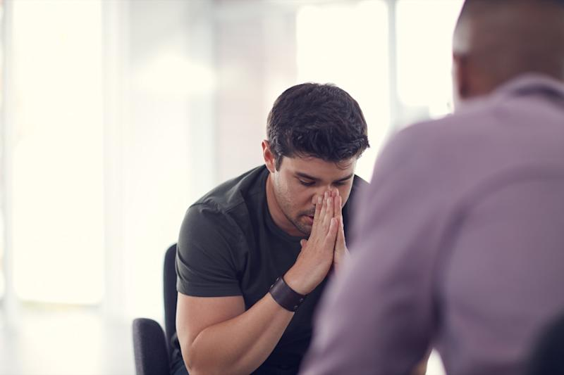 Shot of an unhappy young man talking with a colleague