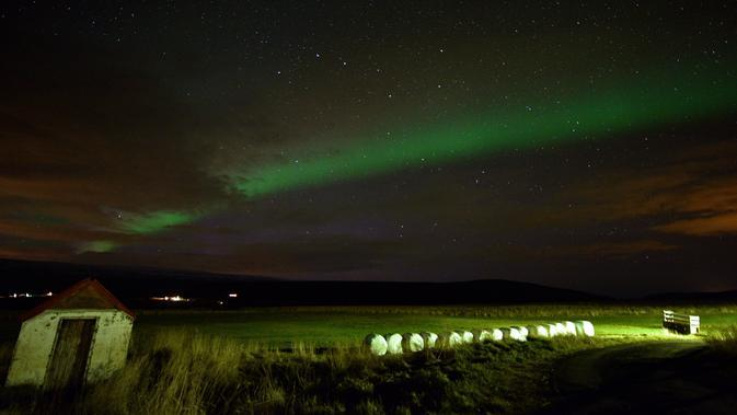 Aurora borealis atau Cahaya Utara terlihat di atas lahan pertanian dekat air terjun Godafoss di Thingeyjarsveit, Islandia, 14 Oktober 2018. Lukisan abstrak alam semesta dari tabrakan spektrum warna Aurora Borealis begitu spektakuler. (Mariana SUAREZ/AFP)