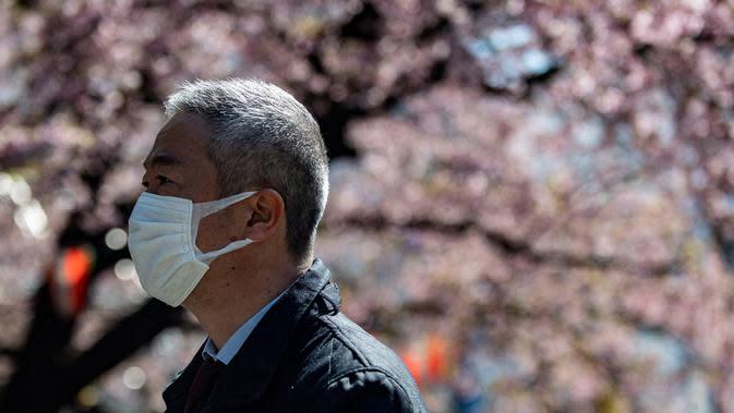 Seorang pria mengenakan masker melewati pohon sakura di taman Ueno, Tokyo (12/3/2020). Hingga Rabu (11/3), Otoritas Tokyo melaporkan 581 kasus, dengan 12 orang meninggal dan 101 sembuh. (AFP/Philip Fong)