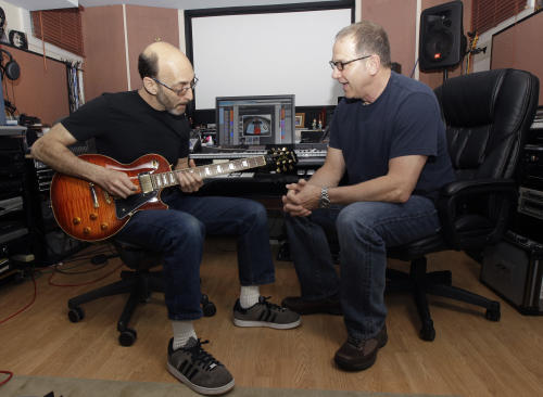 "Musicians Larry Gates, right, and Gerry Polci talk about Polci's new guitar inside Gates' studio, Sunday, May 13, 2012 in Fair Lawn, N.J. The two are part of the Four Seasons band, which is going on tour. Material original to the band has been playing to sold-out crowds on Broadway for the last several years in ""Jersey Boys."" (AP Photo/Julio Cortez)"