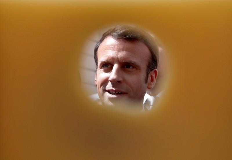 FILE PHOTO: French President Emmanuel Macron is pictured through a piece of cheese as he attends the annual May Day ceremony during which French food products are displayed at the Elysee Palace, in Paris