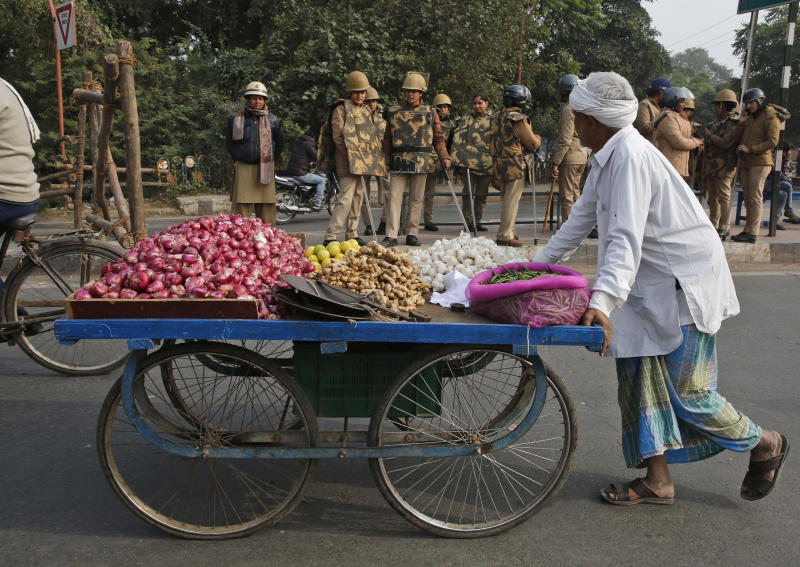 A vegetable vendor pushes his cart past police personnel standing guard on a street in Lucknow, in the northern Indian state of Uttar Pradesh, Friday, Dec. 27, 2019. Paramilitary and police forces were deployed and the internet shut down Friday in Muslim-majority districts in Uttar Pradesh, where more than a dozen people have been killed and more than 1,000 people arrested in protests that have erupted nationwide against a new citizenship law that excludes Muslims. (AP Photo/Rajesh Kumar Singh)