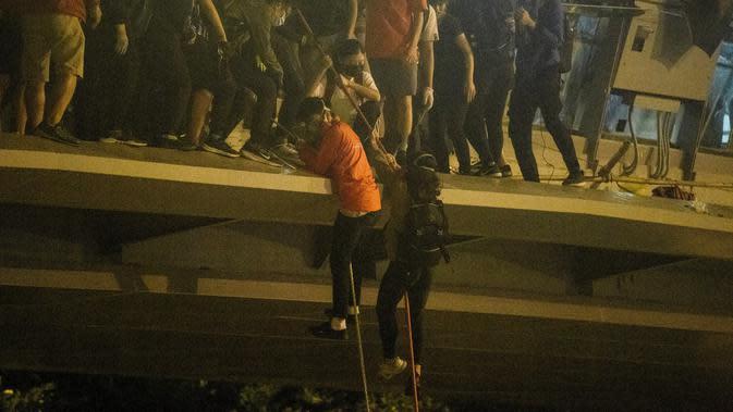 Demonstran menuruni jembatan menggunakan tali untuk melarikan diri dari Universitas Politeknik Hong Kong di Distrik Hung Hom, Hong Kong, Senin (18/11/2019). Lusinan demonstran melarikan diri dari Universitas Politeknik Hong Kong yang dikepung polisi selama berhari-hari. (ANTHONY WALLACE/AFP)