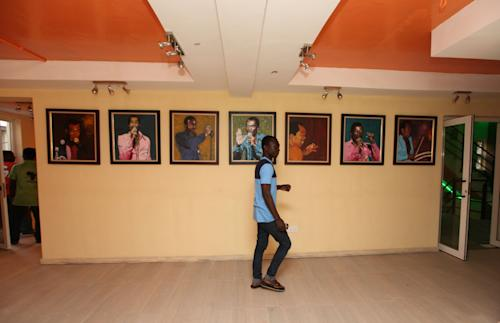 A man walks past portraits of late Afrobeat Legend Fela Kuti, at Kalakuta Museum in Lagos, Nigeria, on Monday, Oct. 15, 2012. The family of late Afrobeat singer Fela Anikulapo-Kuti celebrated the opening of the Kalakuta Museum on Monday in Lagos in the home the musician once lived in. The opening of the museum comes during Felabration, an annual music festival honoring the singer. (AP Photo/Sunday Alamba)